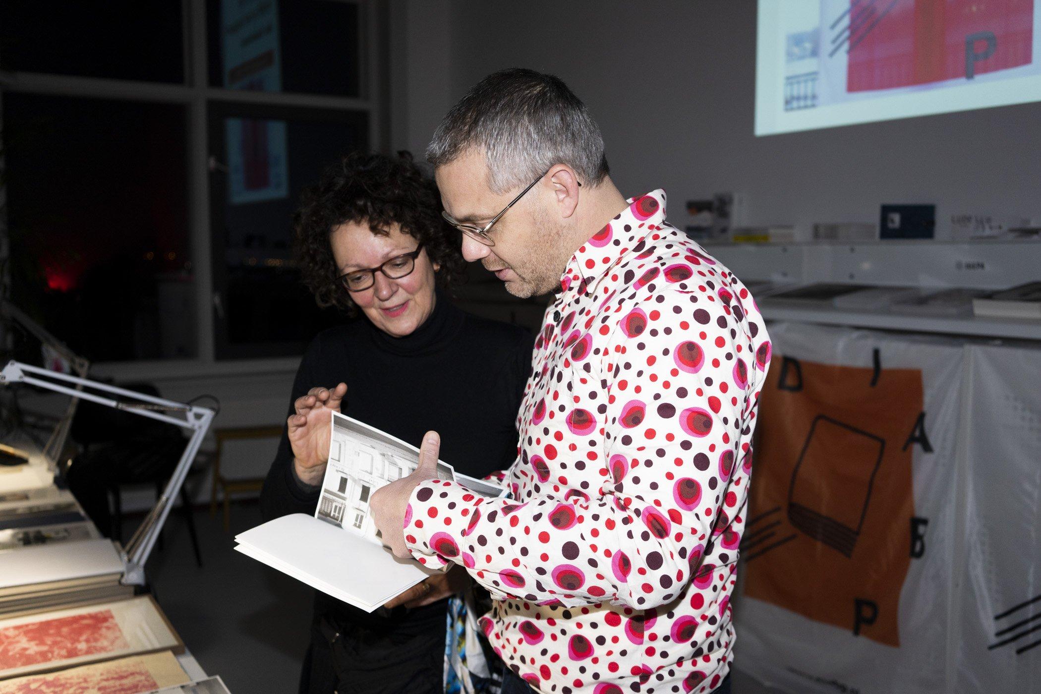Twee bezoekers in gesprek tijden de kerstborrel de Monsterkamer met DIABP en de Fotograaf des Vaderlands